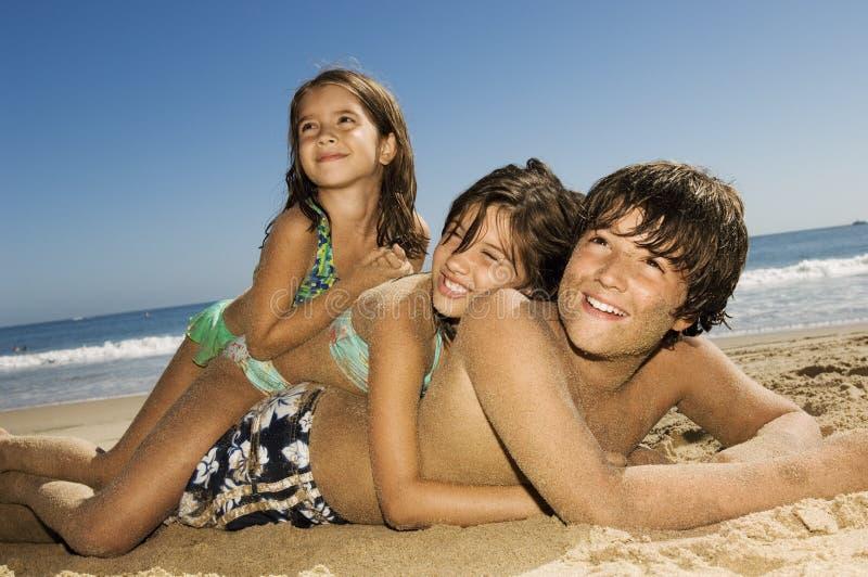 Παιδιά που βρίσκονται πάνω από μεταξύ τους στην παραλία στοκ εικόνα με δικαίωμα ελεύθερης χρήσης
