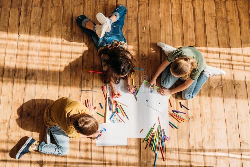 Παιδιά που επισύρουν την προσοχή σε χαρτί με τα μολύβια στο πάτωμα στοκ φωτογραφίες με δικαίωμα ελεύθερης χρήσης