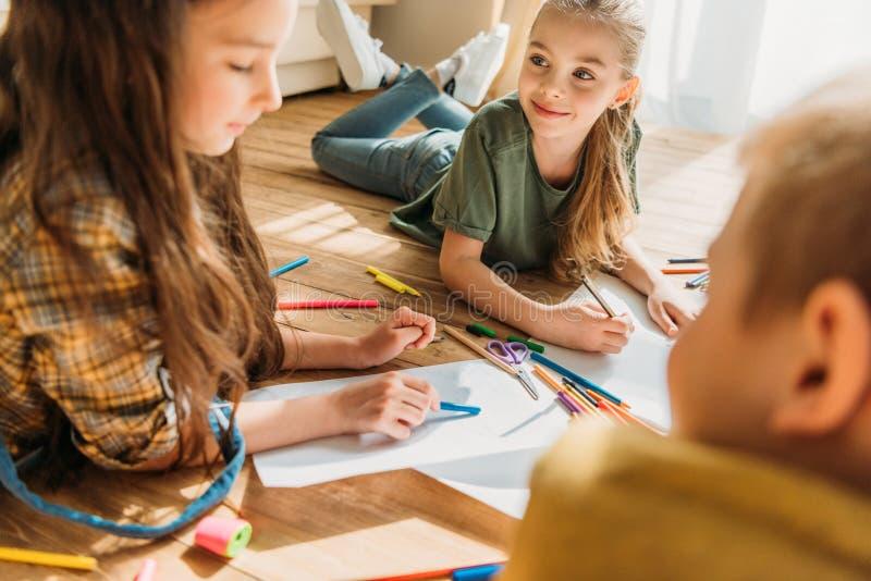 Παιδιά που επισύρουν την προσοχή σε χαρτί με τα μολύβια στο πάτωμα στοκ εικόνες