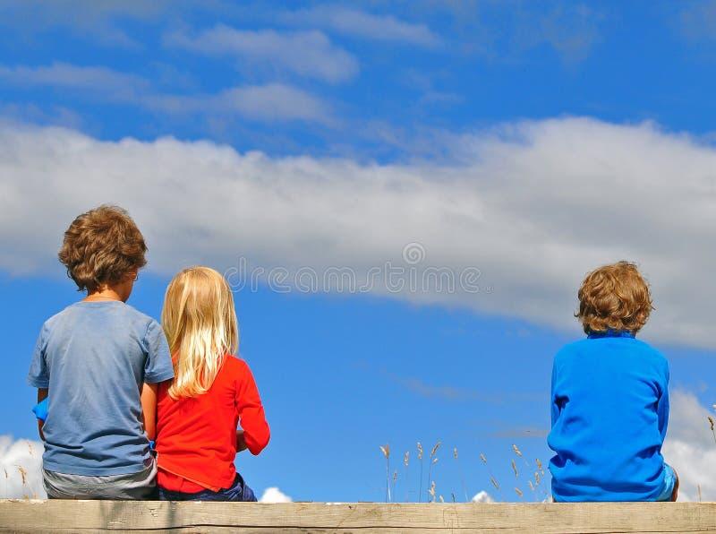 Παιδιά που κάθονται πέρα από τον ουρανό στοκ εικόνες με δικαίωμα ελεύθερης χρήσης