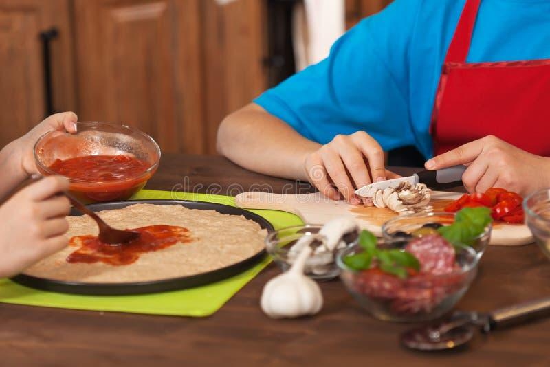 Παιδιά που κατασκευάζουν μια πίτσα στο σπίτι - που διαδίδει τη σάλτσα πιτσών στοκ εικόνες