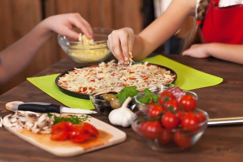 Παιδιά που κατασκευάζουν μια πίτσα στο σπίτι - που διαδίδει το τεμαχισμένο τυρί στοκ εικόνες με δικαίωμα ελεύθερης χρήσης