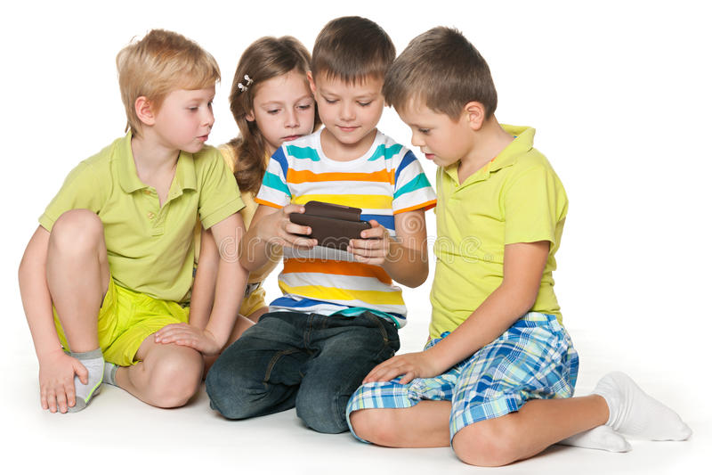 Παιδιά που με μια συσκευή στοκ εικόνα