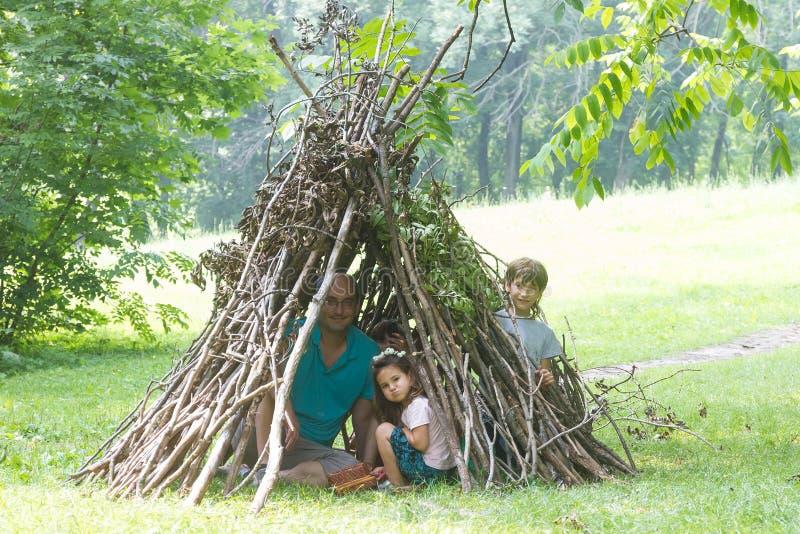 Παιδιά που παίζουν δίπλα ξύλινο να μοιάσει σπιτιών ραβδιών με την ινδική καλύβα, στοκ εικόνες