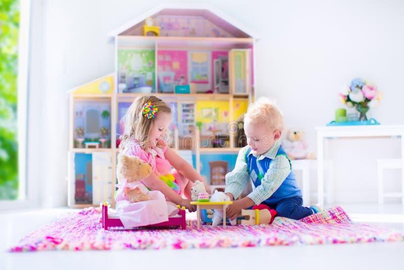 Παιδιά που παίζουν με τα γεμισμένα ζώα και το σπίτι κουκλών στοκ φωτογραφία με δικαίωμα ελεύθερης χρήσης
