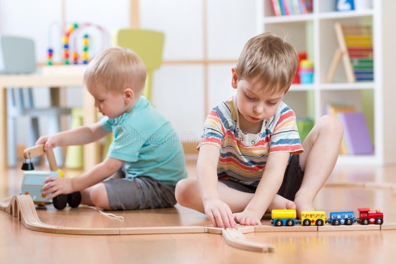 Παιδιά που παίζουν με τα εκπαιδευτικούς παιχνίδια και το δρόμο ραγών οικοδόμησης στοκ εικόνα με δικαίωμα ελεύθερης χρήσης