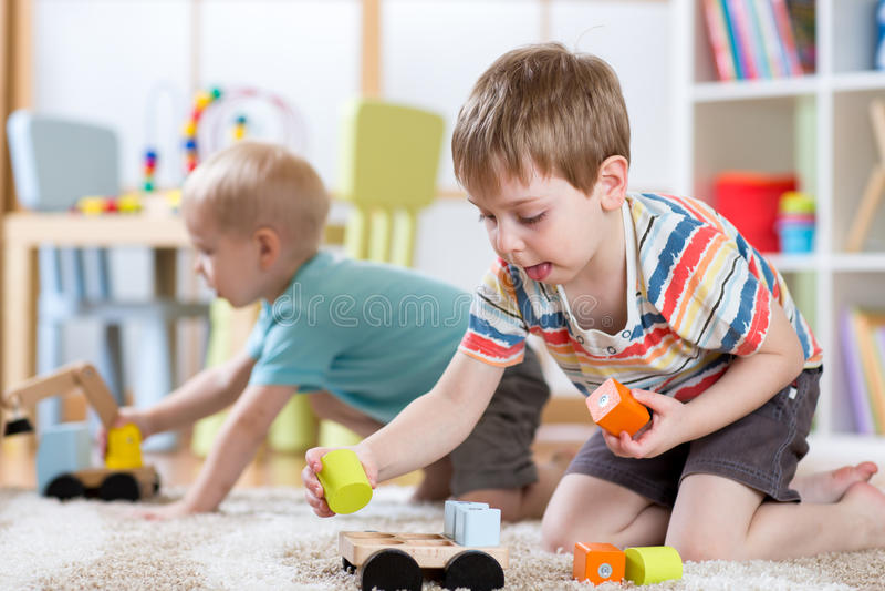 Παιδιά που παίζουν με τα παιχνίδια στον παιδικό σταθμό ή τη φύλαξη ή το σπίτι στοκ εικόνες