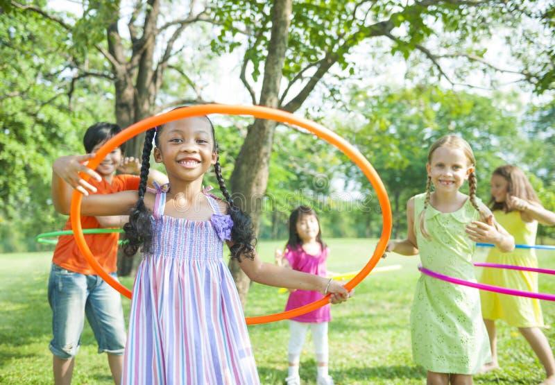 Παιδιά που παίζουν με τις στεφάνες Hoola στοκ εικόνες