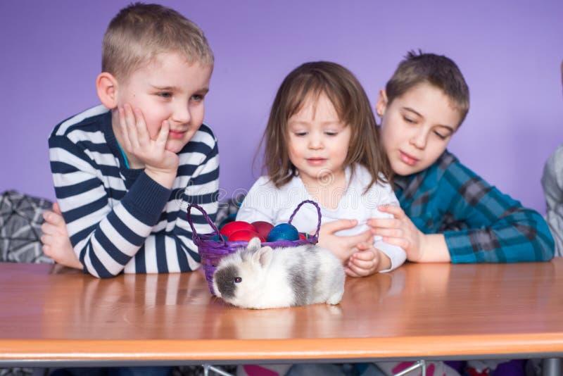 Παιδιά που παίζουν με το λαγουδάκι Πάσχας στοκ εικόνες