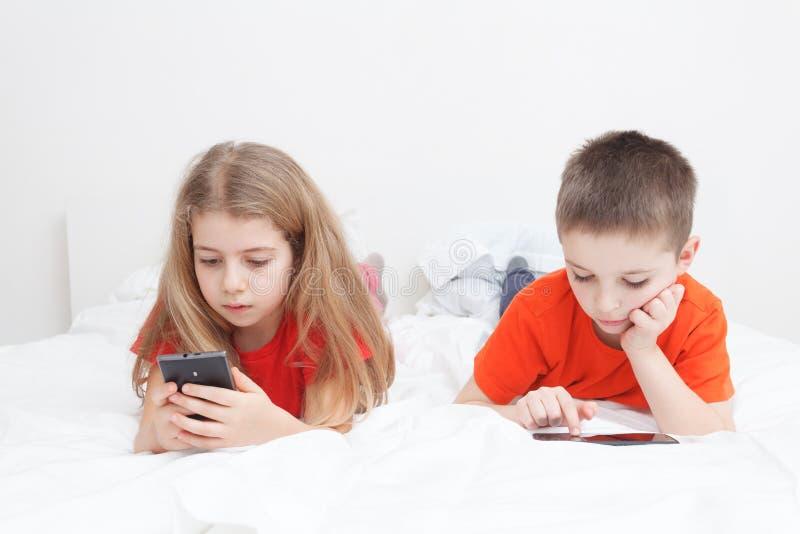 Παιδιά που παίζουν με το smartphone στοκ φωτογραφία