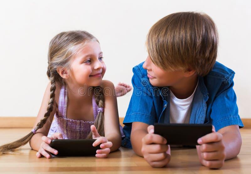 Παιδιά που παίζουν στα κινητά τηλέφωνα στοκ εικόνα