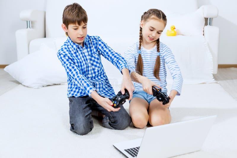 Παιδιά που παίζουν την κονσόλα παιχνιδιών στοκ εικόνες με δικαίωμα ελεύθερης χρήσης