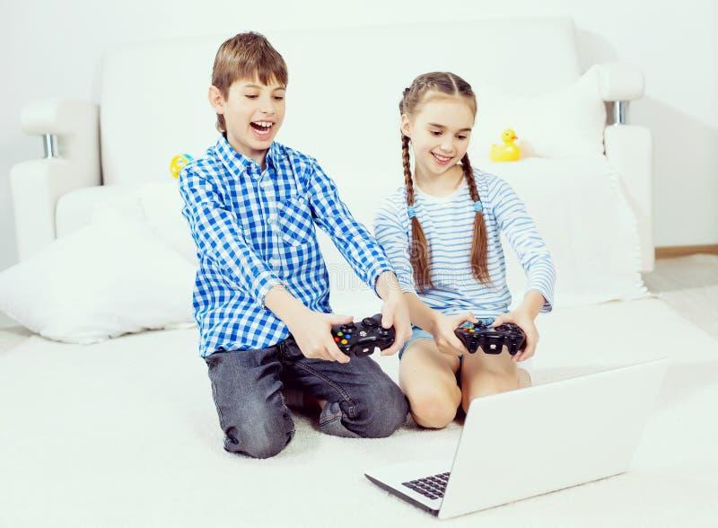Παιδιά που παίζουν την κονσόλα παιχνιδιών στοκ εικόνα με δικαίωμα ελεύθερης χρήσης