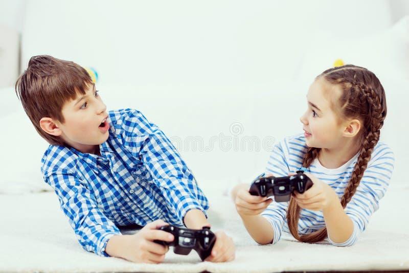 Παιδιά που παίζουν την κονσόλα παιχνιδιών στοκ εικόνες