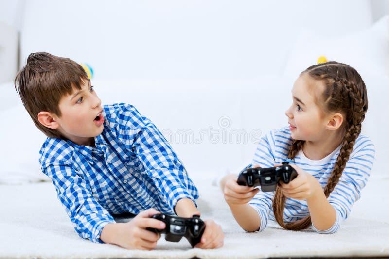 Παιδιά που παίζουν την κονσόλα παιχνιδιών στοκ φωτογραφία