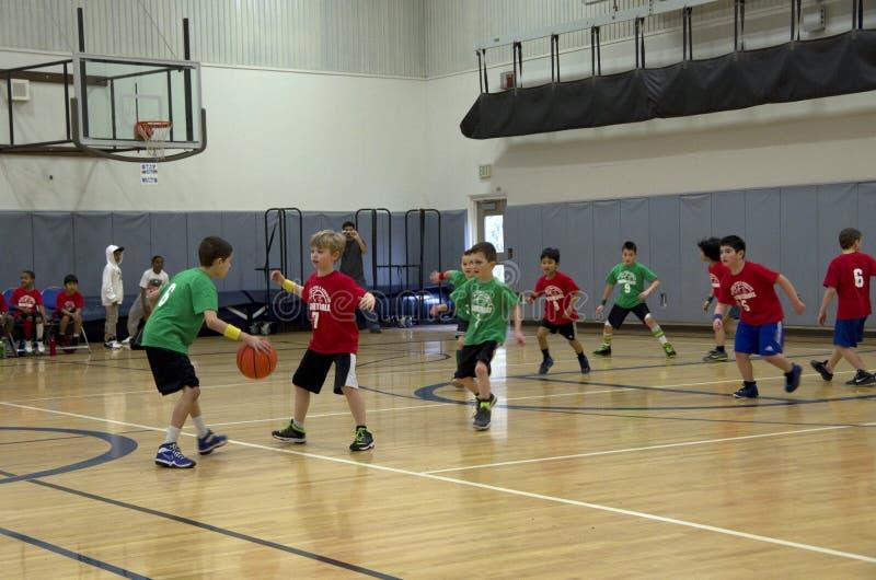Παιδιά που παίζουν τον αγώνα καλαθοσφαίρισης στοκ εικόνα