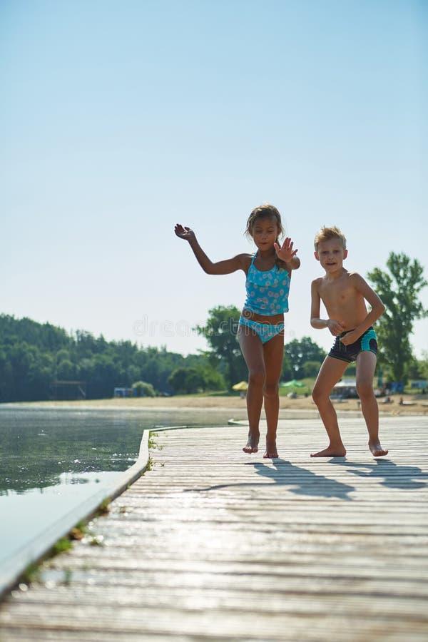 Παιδιά που παίζουν το καλοκαίρι σε μια αποβάθρα στοκ φωτογραφίες με δικαίωμα ελεύθερης χρήσης