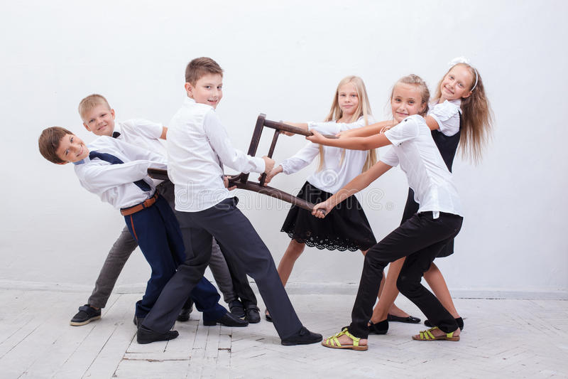 Παιδιά που παίζουν το ρυμουλκό της καρέκλας - κορίτσια εναντίον των αγοριών στοκ φωτογραφίες