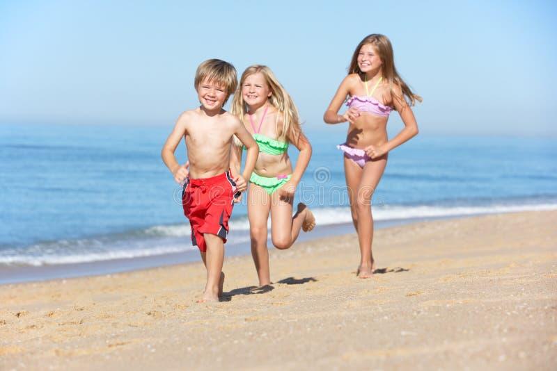 Παιδιά που τρέχουν κατά μήκος της θερινής παραλίας στοκ εικόνες