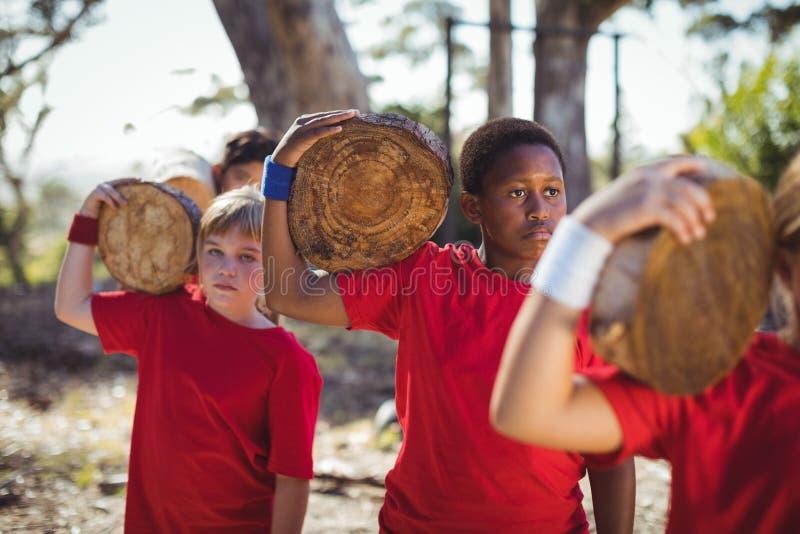 Παιδιά που φέρνουν το ξύλινο κούτσουρο κατά τη διάρκεια της κατάρτισης σειράς μαθημάτων εμποδίων στοκ εικόνες