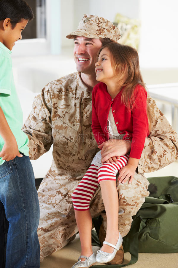 Παιδιά που χαιρετούν το στρατιωτικό σπίτι πατέρων στην άδεια στοκ φωτογραφία με δικαίωμα ελεύθερης χρήσης