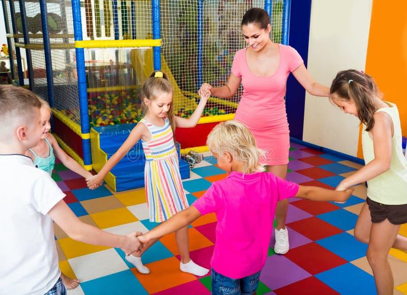 Παιδιά που χορεύουν με το δάσκαλο στη μουσική στην κατηγορία στο σχολείο στοκ εικόνα