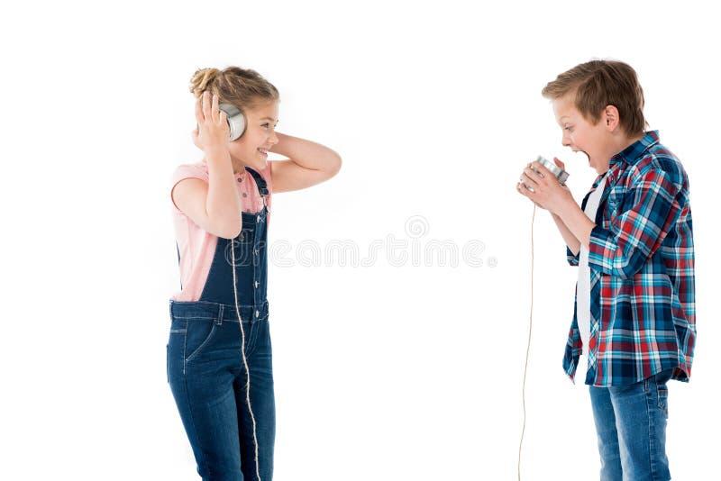 Παιδιά που χρησιμοποιούν τα φλυτζάνια μετάλλων ως τηλέφωνο παίζοντας από κοινού στοκ φωτογραφίες με δικαίωμα ελεύθερης χρήσης