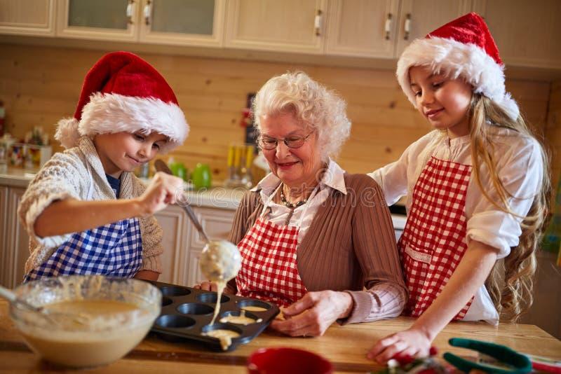 Παιδιά που ψήνουν τα μπισκότα με τη γιαγιά στα Χριστούγεννα στοκ εικόνα με δικαίωμα ελεύθερης χρήσης