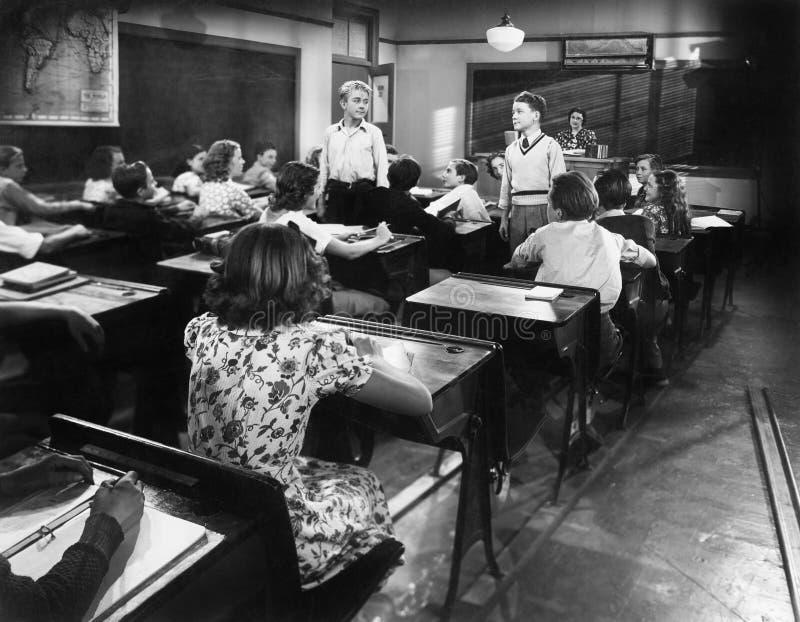 Παιδιά σε ένα δωμάτιο κατηγορίας με δάσκαλο και δύο αγόρια που εξετάζουν το ένα το άλλο (όλα τα πρόσωπα που απεικονίζονται δεν ζο στοκ εικόνες