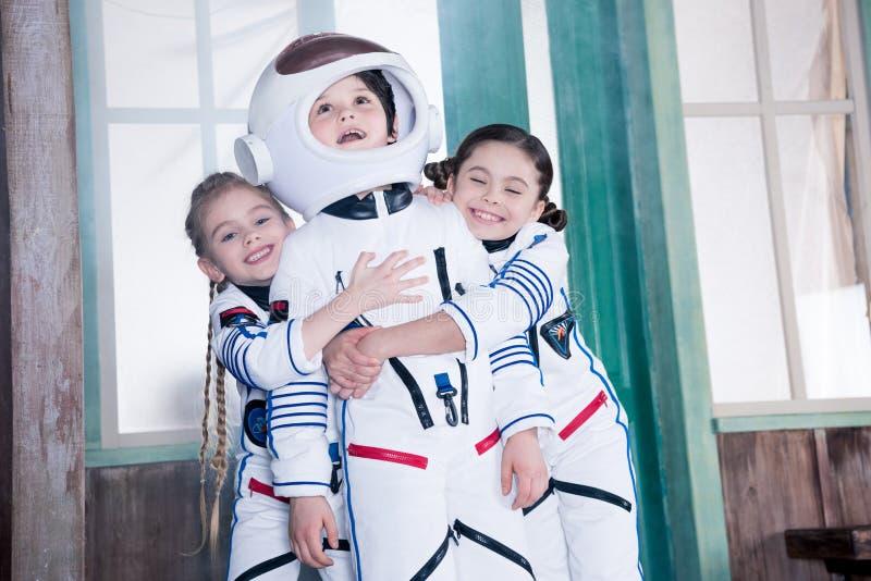 Παιδιά στα κοστούμια αστροναυτών, κορίτσια που αγκαλιάζουν το αγόρι στοκ φωτογραφίες με δικαίωμα ελεύθερης χρήσης