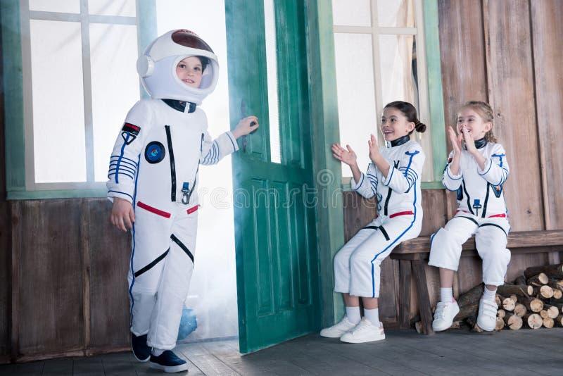 Παιδιά στα κοστούμια αστροναυτών, κορίτσια που επιδοκιμάζουν στο αγόρι στοκ εικόνες