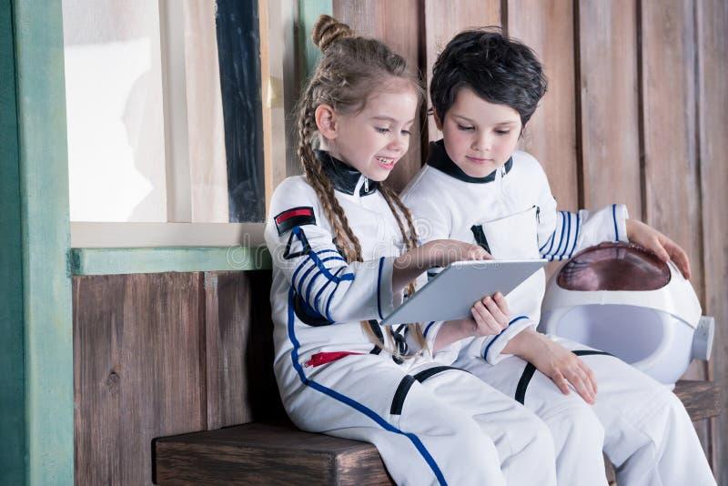 Παιδιά στα κοστούμια αστροναυτών που χρησιμοποιούν την ψηφιακή ταμπλέτα στοκ φωτογραφίες