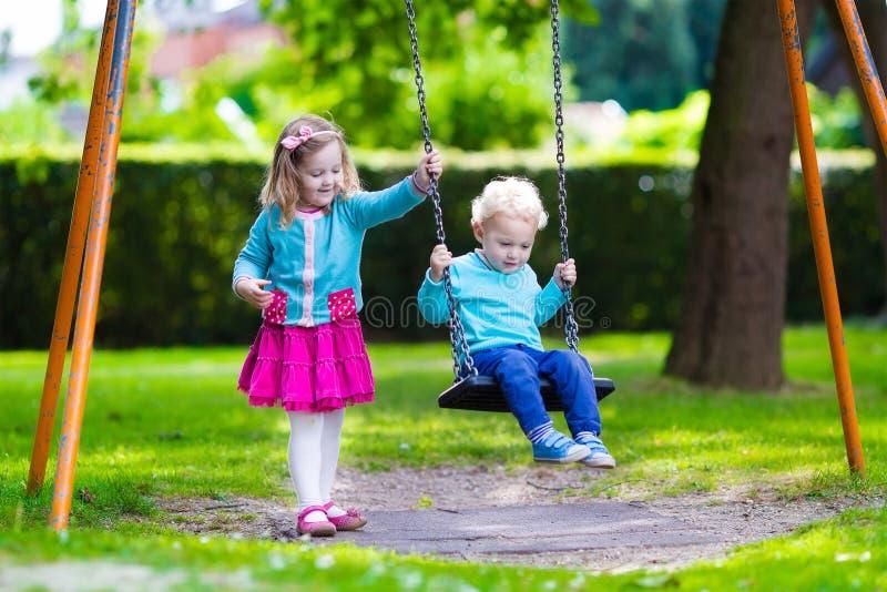 Παιδιά στην ταλάντευση παιδικών χαρών στοκ φωτογραφία