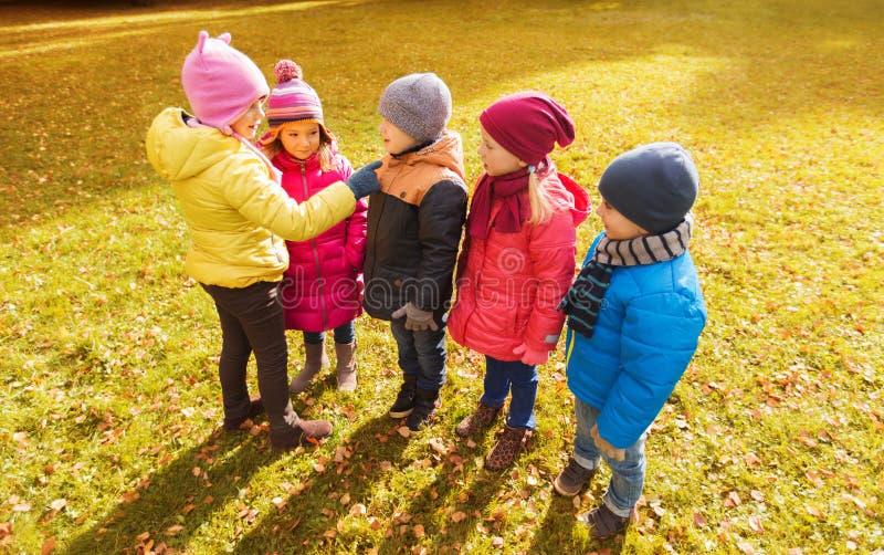 Παιδιά στο πάρκο φθινοπώρου που μετρά και που επιλέγει τον ηγέτη στοκ εικόνα