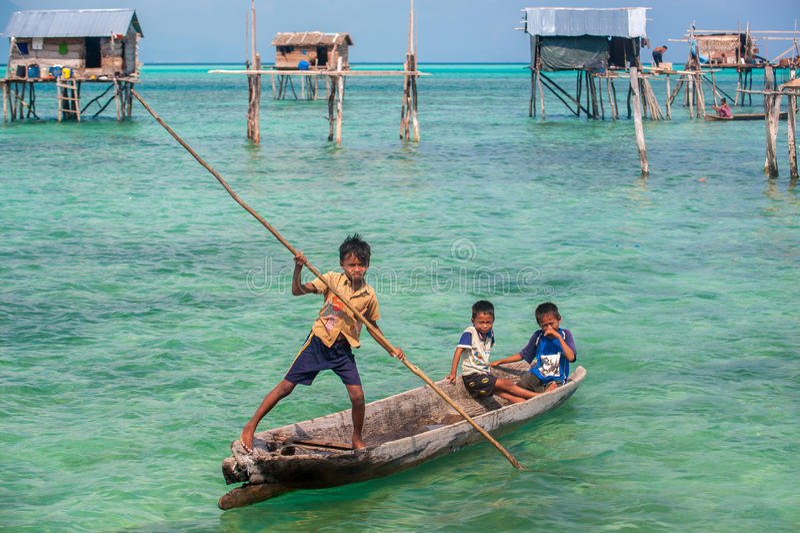 Παιδιά τσιγγάνων θάλασσας σε sampan τους με το σπίτι τους στα ξυλοπόδαρα στοκ φωτογραφίες με δικαίωμα ελεύθερης χρήσης