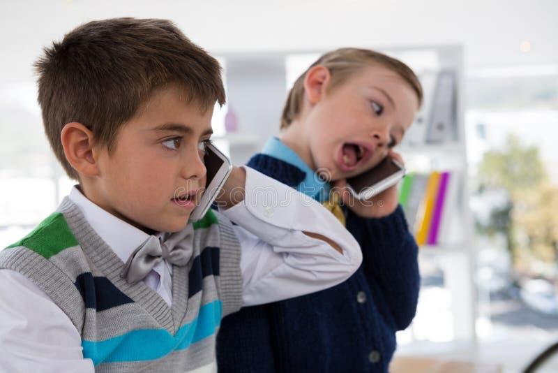 Παιδιά ως ανώτατα στελέχη επιχείρησης που μιλούν στο κινητό τηλέφωνο στοκ εικόνες με δικαίωμα ελεύθερης χρήσης