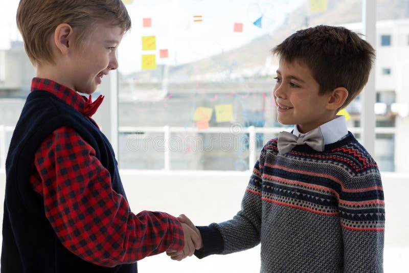 Παιδιά ως ανώτατα στελέχη επιχείρησης που τινάζουν τα χέρια στοκ φωτογραφίες