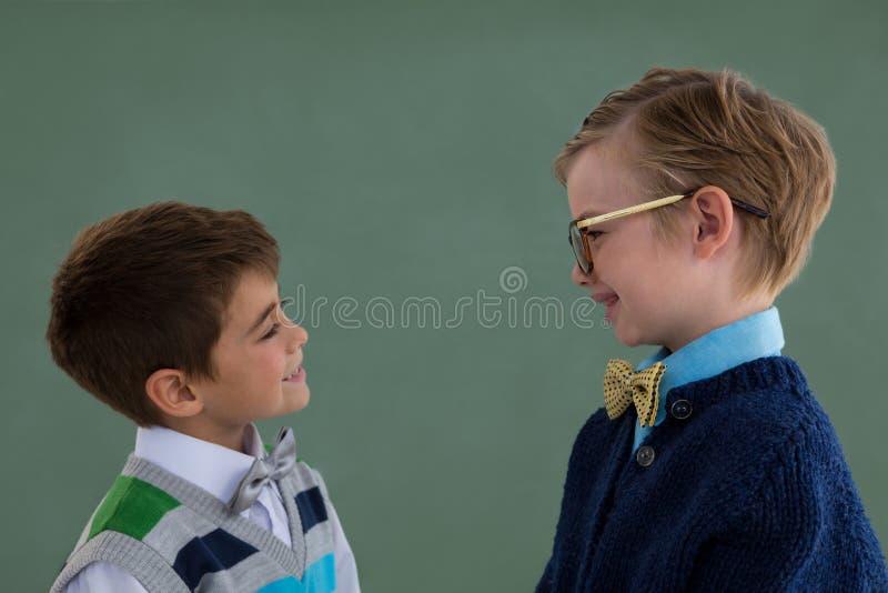 Παιδιά ως ανώτατο στέλεχος επιχείρησης που χαμογελά στεμένος στοκ εικόνα