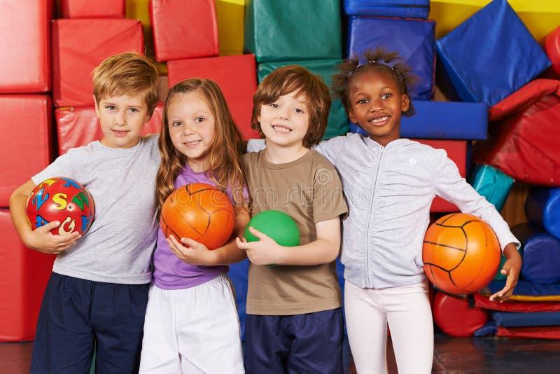 Παιδιά ως ομάδα με τις σφαίρες στη γυμναστική στοκ εικόνες