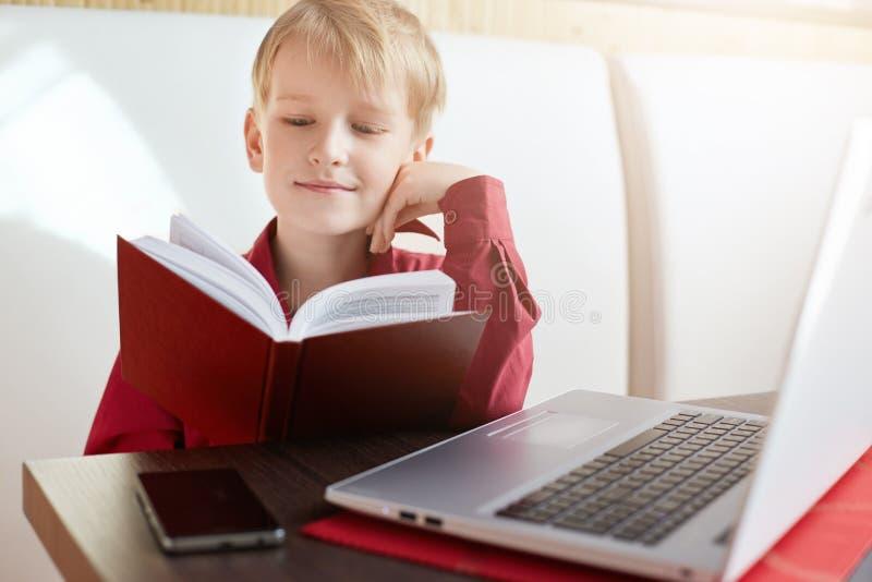 Παιδική ηλικία και ελεύθερος χρόνος Ένα πορτρέτο της σοβαρής συνεδρίασης μικρών παιδιών μπροστά από το ανοικτό σημειωματάριο που  στοκ εικόνα με δικαίωμα ελεύθερης χρήσης
