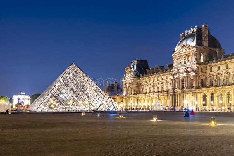 Παλάτι και πυραμίδες του Λούβρου τη νύχτα, Παρίσι, Γαλλία στοκ εικόνες