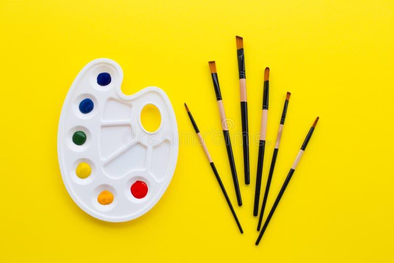 Παλέτα και βούρτσες στο κίτρινο υπόβαθρο στοκ εικόνες με δικαίωμα ελεύθερης χρήσης