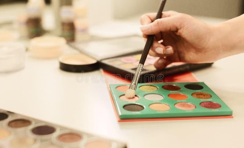 Παλέτες βουρτσών και σκιάς ματιών εκμετάλλευσης καλλιτεχνών Makeup που βρίσκονται στον πίνακα στοκ εικόνες