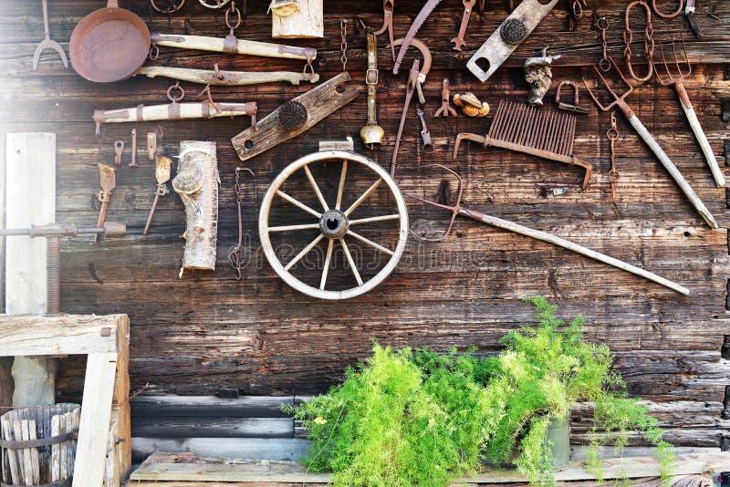 Παλαιά αγροτικά εργαλεία, που κρεμούν στον ξύλινο τοίχο του σπιτιού στοκ εικόνες με δικαίωμα ελεύθερης χρήσης