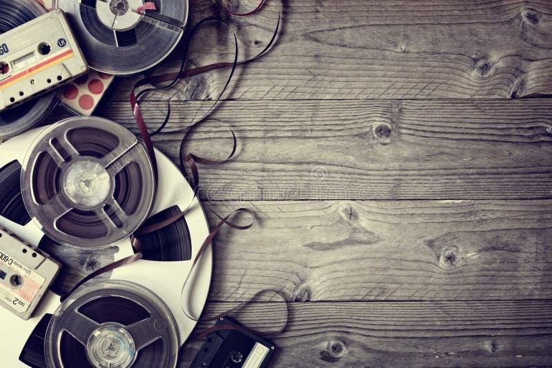 Παλαιά ακουστικά εξέλικτρα και υπόβαθρο ταινιών κασετών στοκ εικόνα με δικαίωμα ελεύθερης χρήσης