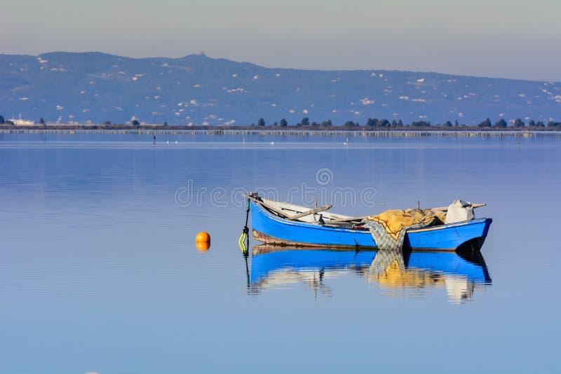 Παλαιά αλιευτικά σκάφη με τα φωτεινά χρώματα στην αυγή στη λίμνη στοκ εικόνα