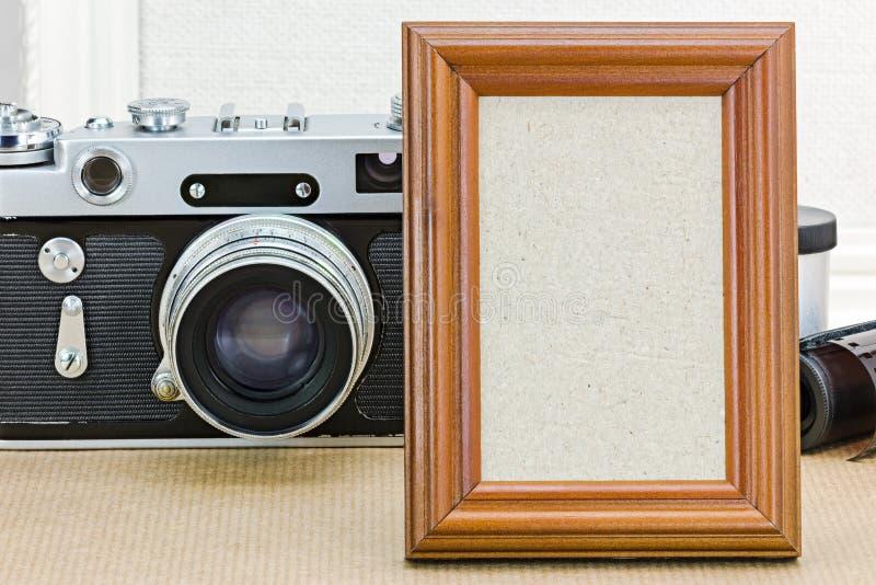 Παλαιά αναδρομική κάμερα και κενό ξύλινο πλαίσιο φωτογραφιών στην ΤΣΕ καφετιού εγγράφου στοκ εικόνα με δικαίωμα ελεύθερης χρήσης