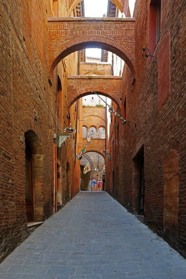 Παλαιά ανηφορική οδός με τα μεσαιωνικά κτήρια στη Σιένα στοκ εικόνες