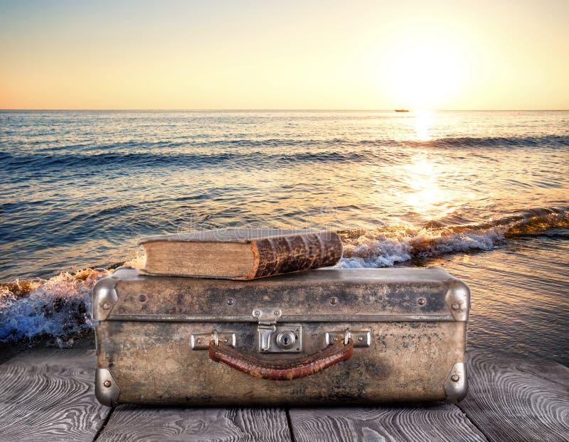Παλαιά βαλίτσα με το βιβλίο στις ξύλινες σανίδες ενάντια στη θάλασσα στοκ εικόνα με δικαίωμα ελεύθερης χρήσης
