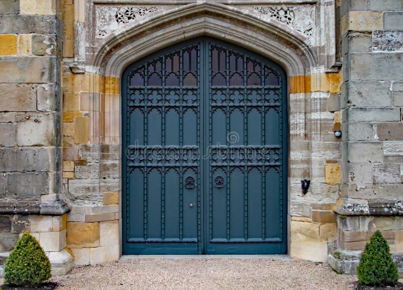 Παλαιά βαριά περίκομψη πόρτα σε ένα παλαιό αγγλικό σπίτι φέουδων στοκ εικόνες